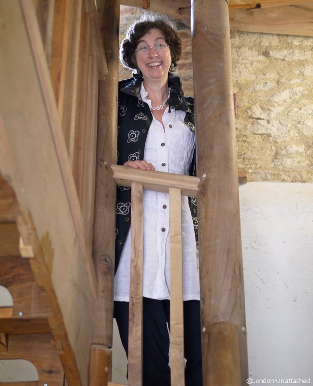 Kate More standing on the staircase she built - Silk Mill Frome