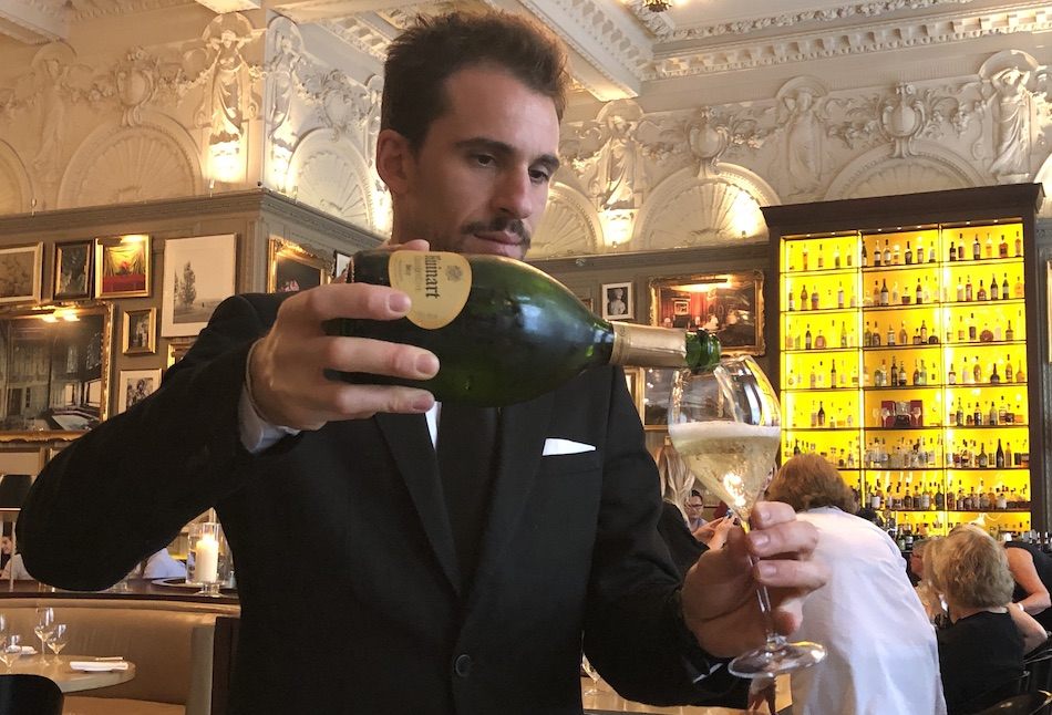 waiter pouring Ruinart brut champagne