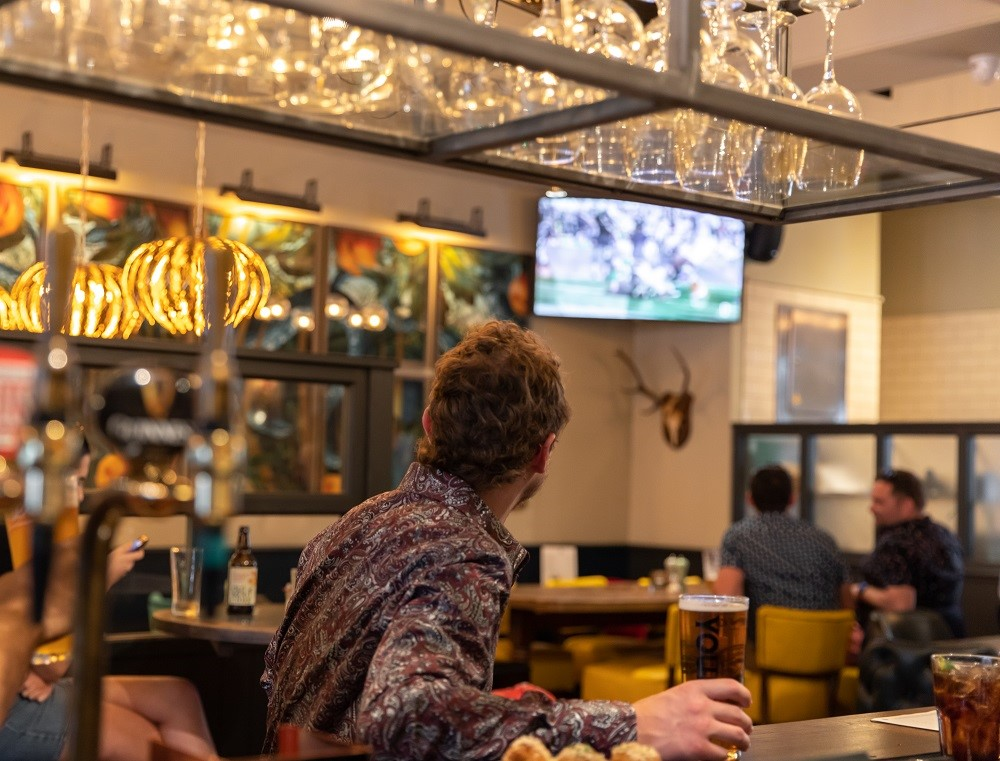 The Adam & Eve pub W1 - interior with customer.