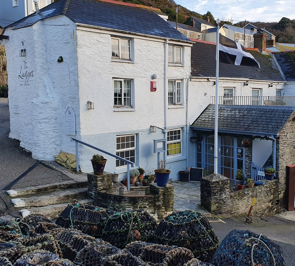 The exterior of the Lugger Hotel, Portloe with Cornish flag and Lobster pots