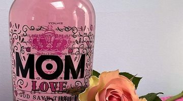 bottle of MOM LOVE branded strawberry flavoured gin and pink roses