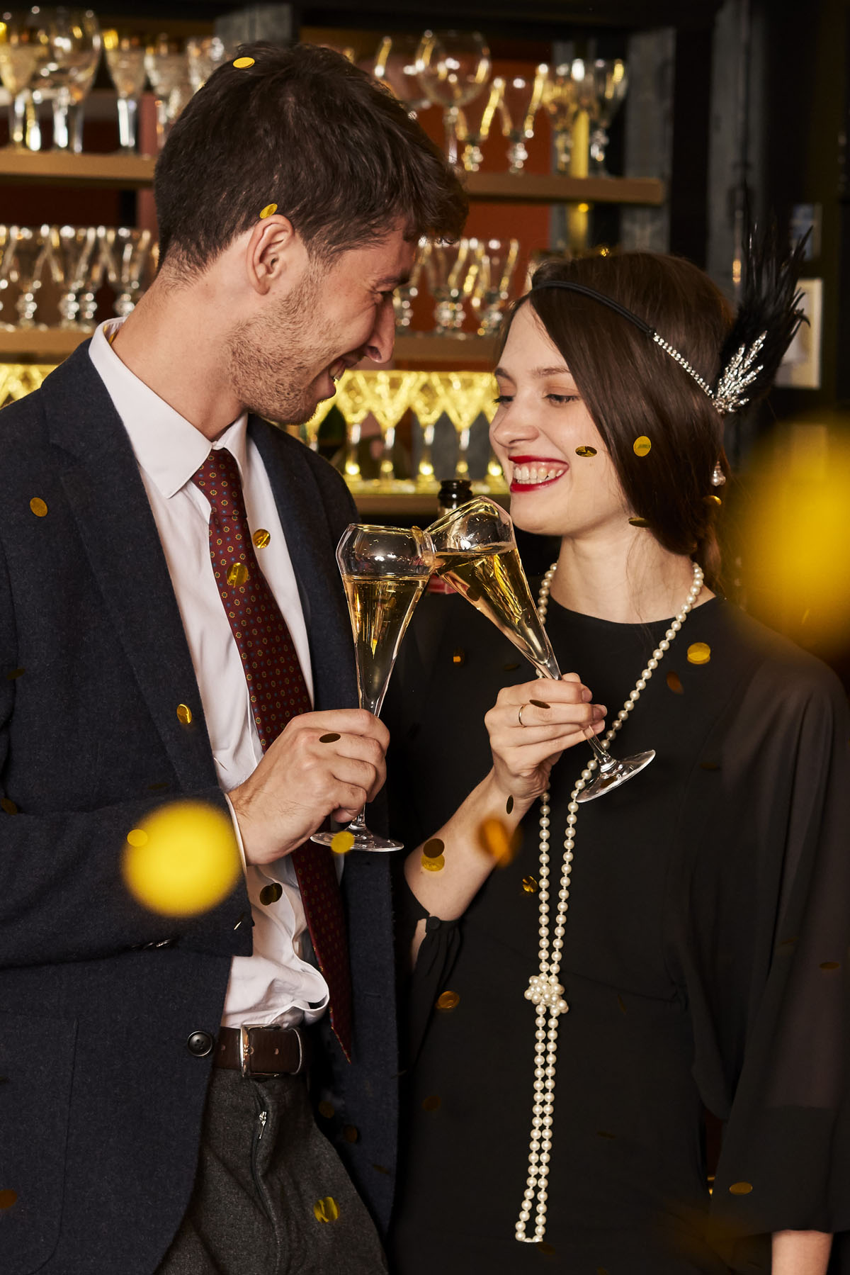 Couple in 1920s clothes drinking Champagne
