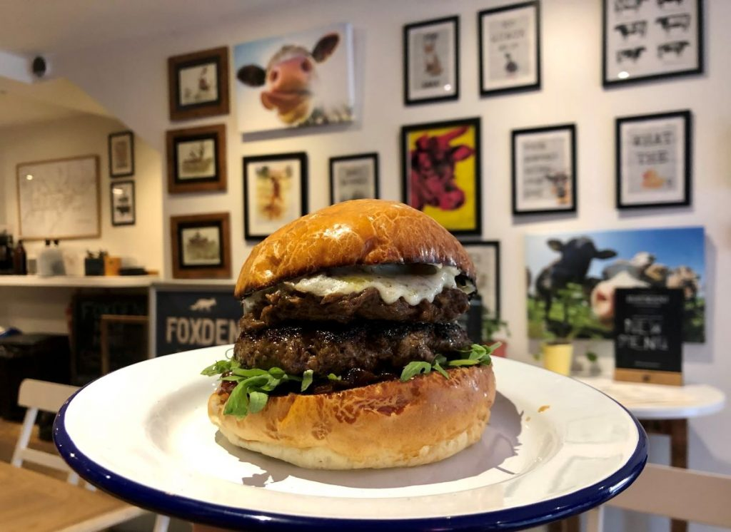 The Foxden burger on a white plate with framed cow pictures on the back wall